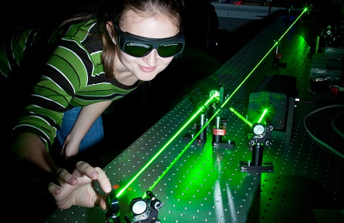 female scientist working with lasers while doing research in a q