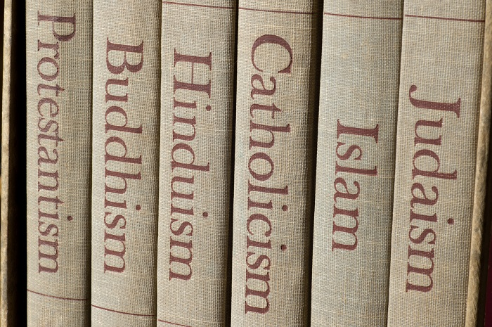 Book spines listing major world religions - Judaism Islam Catholicism Hinduism Buddhism and Protestantism.