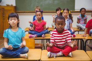 Pupils meditating in lotus position on desk in classroom at the