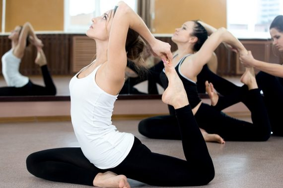Two Yogi Female Exercising In Class